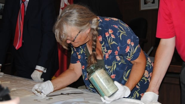 Basia Baklinski, conservator from Lang Pioneer Village Museum, handles the time capsule.