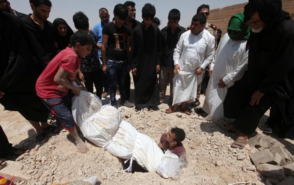 IRAQ Wadi al-Salam Peace Valley CEMETERY Men bury body