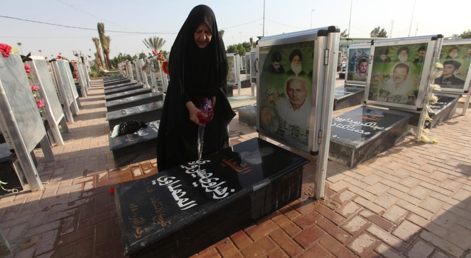 IRAQ Peace Valley CEMETERY woman washes grave of relative