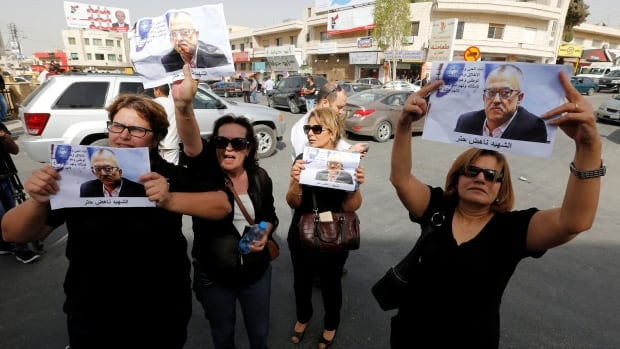 Relatives and friends of Nahed Hattar hold pictures of him during a sit-in in the town of Al-Fuheis near Amman on Sunday.<br />