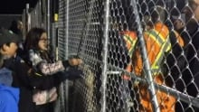 Kid protesters and Muskrat Falls workers separated by a gate