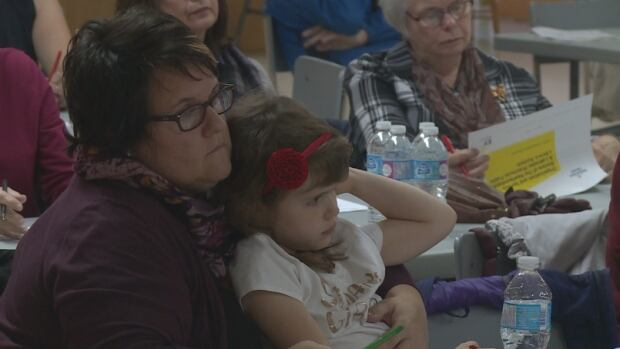 Paula Gale sits with her daughter during the public libraries consultation in Twillingate on Thursday.
