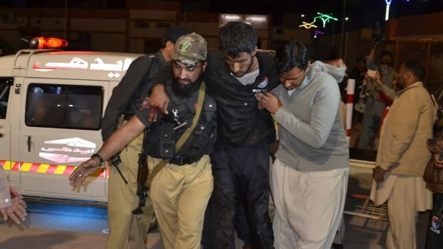 A Pakistani volunteer and a police officer rush an injured person to a hospital in Quetta, Pakistan, on Monday after gunmen attacked a police training centre.