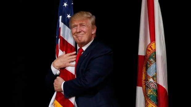 trump hugs flag oct 24