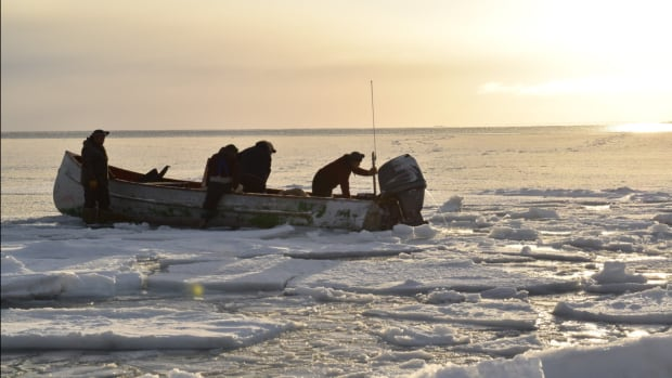 Hunters pack their boat from the shore in Igloolik. The mysterious sound has been noted by hunters in the area of Hecla and Fury Strait, a rich hunting ground that they say was empty this year. (Nick Murray/CBC)