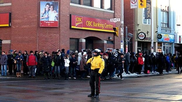 A Toronto police officer directs traffic in downtown Toronto as commuters line up for emergency bus service.