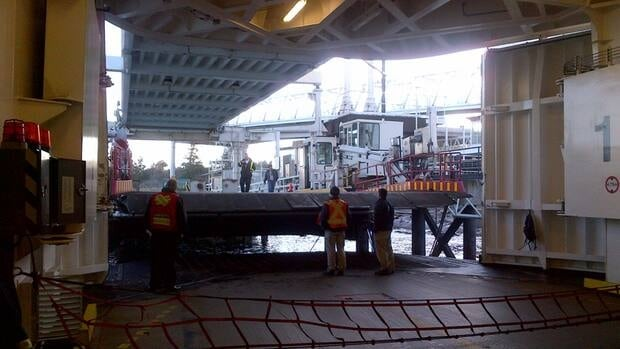 Crew members inspect the areas of impact after the BC Ferries vessel Coastal Inspiration made a hard landing while trying to dock at Duke Point on Tuesday.