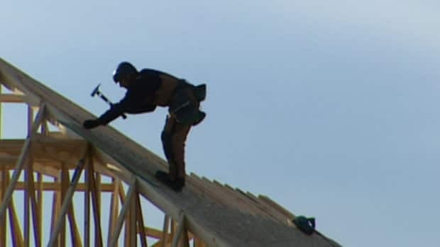 A roofer works works on a new housing development. Some developers say they're worried Charlottetown's new water rules will run them out of business.