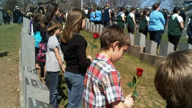 Children stand behind gravestones for each of the Titanic victims buried in Fairview Lawn Cemetery, Halifax on the 100th anniversary of the ship's sinking.