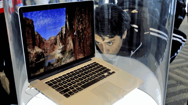 An attendee looks at the new MacBook Pro on display at the Apple World Developers Conference on June 11. Prices for the 13-inch model will be $1,199 to $1,499, while a 15-inch model will be $1,799 or $2,199, depending on the amount of storage.
