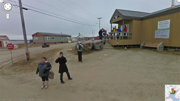 A group of people leaving the visitor's centre in Cambridge Bay take photos of the Google Street View tricycle and its 360 degree camera as it went by in August. Google will photograph Iqaluit next week using cameras mounted on backpacks.
