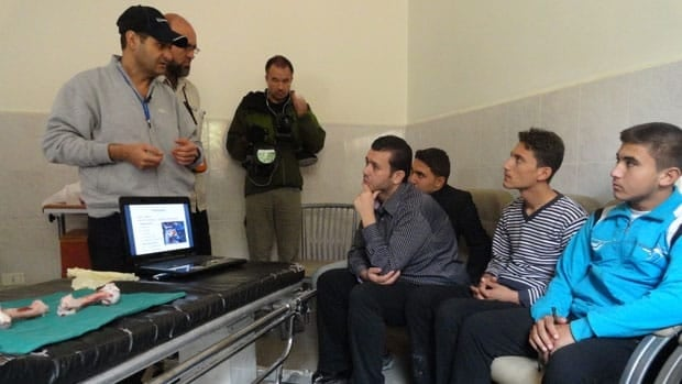 Dr. Jay Dahman, wearing ballcap, trains medical workers at the main hospital in Anadan, Syria. The Toronto-based doctor uses sheep bones in his demonstrations.