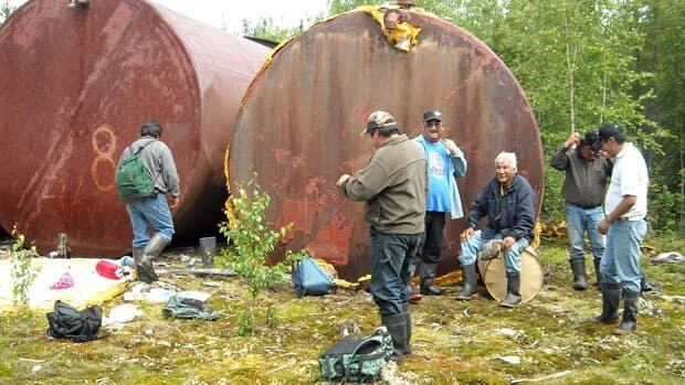 Sachigo Lake First Nation members clean up around abandoned fuel tanks at the old Lingman Lake mine site near their community.