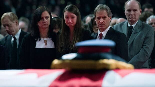 Const. Jennifer Kovach's sister Emily Kovach, second left, and father Bill Kovach, second right, look on during her funeral in Guelph, Ont., on Thursday.