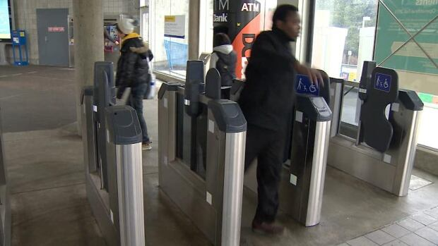 A man walks through open fare gates in 2013 at a SkyTrain station. Full operation for the gates and the accompanying Compass Card system have been pushed back numerous times over almost a decade.