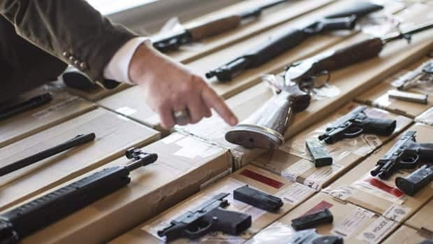 A police officer points out some of the firearms seized during the Project Traveller raids.
