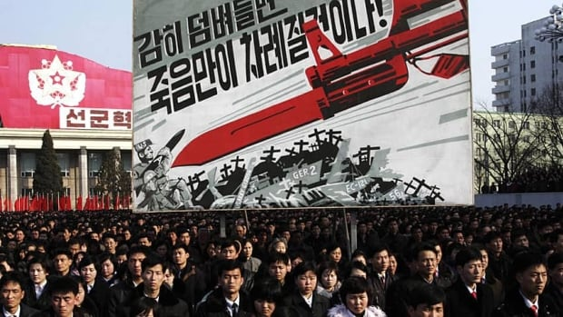 The billboard at this North Korean rally depicts a large bayonet pointing at U.S. army soldiers with writing reading 'If you dare invade, only death will be waiting for you!'