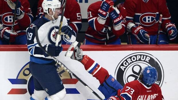 Montreal Canadiens right wing Brendan Gallagher  is knocked to the ice by Winnipeg Jets center Jim Slater during first period of Tuesday's game in Montreal.