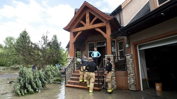 Calgary firefighters check on homes as residents and volunteers clean up in the community of Bowness June 24.
