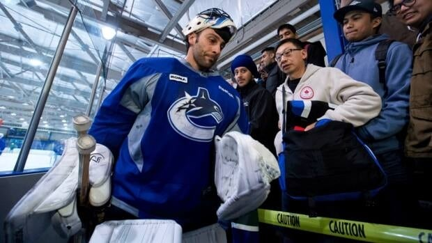 Vancouver Canucks' goalie Roberto Luongo walks past fans as after an informal practice with teammates at the University of British Columbia in Vancouver on Friday.