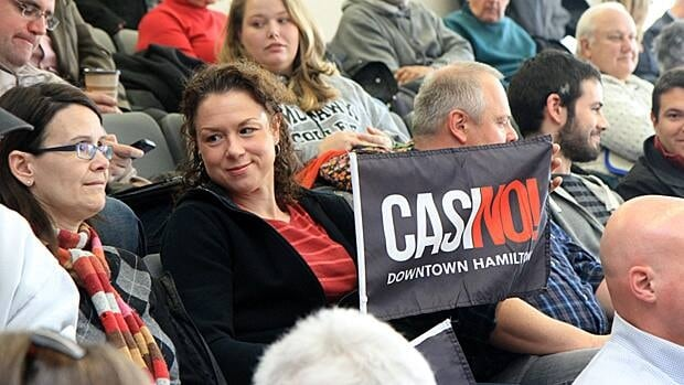 Rochelle Martin sits in the audience of a council meeting Thursday holding a sign opposing a casino. Councillors voted for a casino in Flamborough as long as it's a viable site. (Samantha Craggs/CBC)