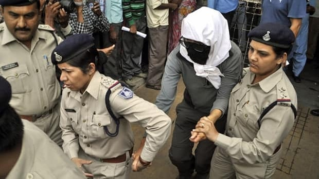 In this March 16 file photo, a Swiss woman, who, according to police, was gang-raped by a group of eight men while touring by bicycle with her husband, is escorted by policewomen for a medical examination at a hospital in Gwalior, in the central Indian state of Madhya Pradesh.