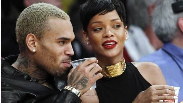 Chris Brown, left, and Rihanna attend an NBA basketball game between the Los Angeles Lakers and New York Knicks in Los Angeles on Dec. 25, 2012. Rihanna has defended reuniting with Brown, but says if he hits her again, he's out.