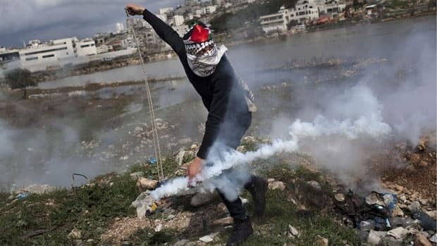 A masked Palestinian throws back a gas canister previously shot by Israeli forces, during a protest to support Palestinian prisoners.