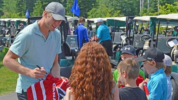 Jordan Staal of the NHL's Carolina Hurricanes signs autographs for some of his Thunder Bay fans at a charity golf tournament on Thursday.