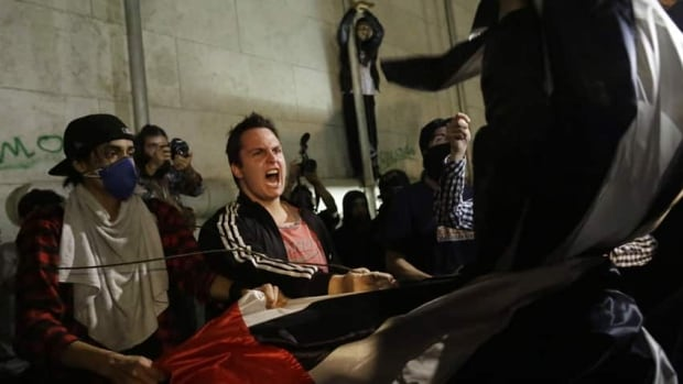 Protestors rip away a Sao Paulo state flag after forcing their way into City Hall in Sao Paulo, Brazil, on Tuesday. Thousands of demonstrators flooded into a square in Brazil's economic hub for the latest in a historic wave of protests.