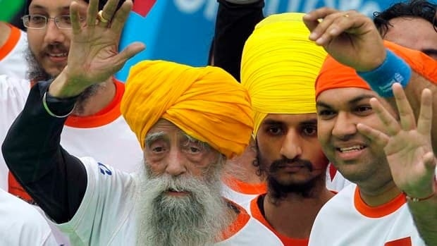 Marathon runner Fauja Singh, 101, left, originally from Beas Pind, in Jalandhar, India but who now lives in London, waves after finishing his 10-kilometre race in Hong Kong.