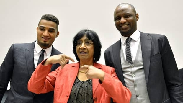 AC Milan's Kevin-Prince Boateng, left, U.N. High Commissioner for Human Rights South African Navanethem Pillay, centre, and Patrick Vieira, right, former captain of the French national football team pose for photos at the panel discussion.