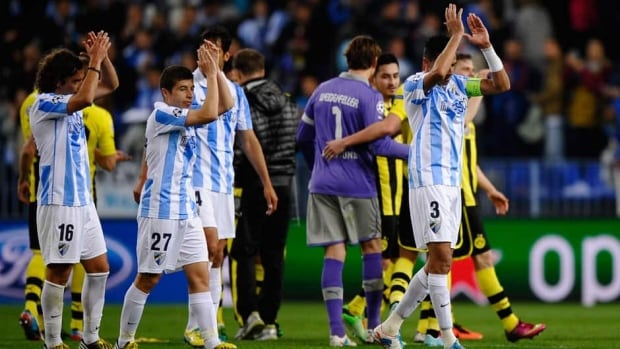 Malaga's Manuel Iturra, Portillo and Weligton from left, acknowledge the supporters after the Champions League quarter-final between Malaga and Borussia Dortmund in Malaga, Spain, Wednesday.