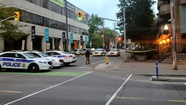 A member of the Ottawa police takes photographs at the scene of a shooting on Laurier Avenue West early Sunday morning.