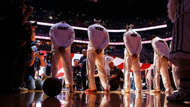 Miami Heat's LeBron James, second left, stands for the national anthem before his team plays the San Antonio Spurs in Game 7 of the NBA Finals on Thursday.