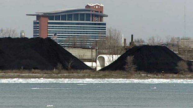 Petroleum coke stands three stories high on the banks of the Detroit River.