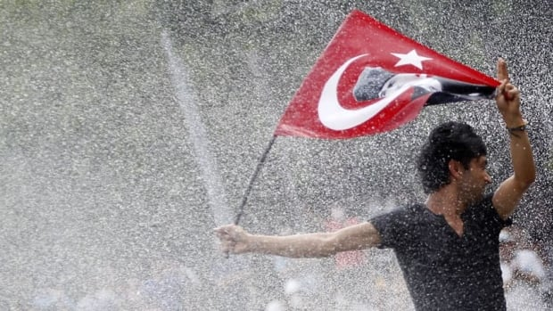 A protester is attacked by water cannon in Kizilay square in central Ankara on Sunday. Unions in the country are calling for a one-day walkout aimed at maintaining pressure on Prime Minister Recep Tayyip Erdogan's government.