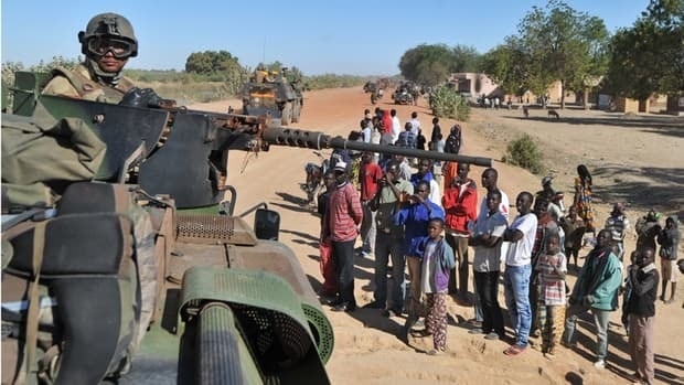A group of Malian youths gather near an armoured vehicle as French soldiers arrive in the town of Diabaly on Monday. Islamic militants retreated after heavy airstrikes from French forces.