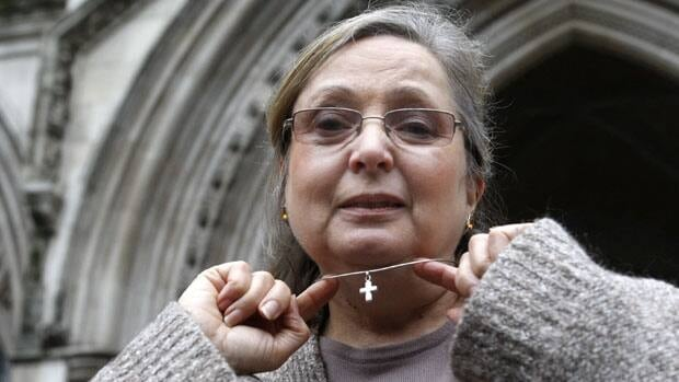 British Airways check-in employee Nadia Eweida shows her Christian cross to the media in 2010. A top European Human Rights court ruled on Tuesday that the airline discriminated against her in November of 2006.