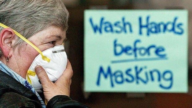 A woman puts on a protective mask to protect against SARS at a wash station at the entrance to North York General Hospital in Toronto in May 2003.