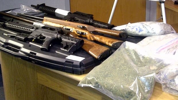 Police show some of the drugs and guns seized in the raids.