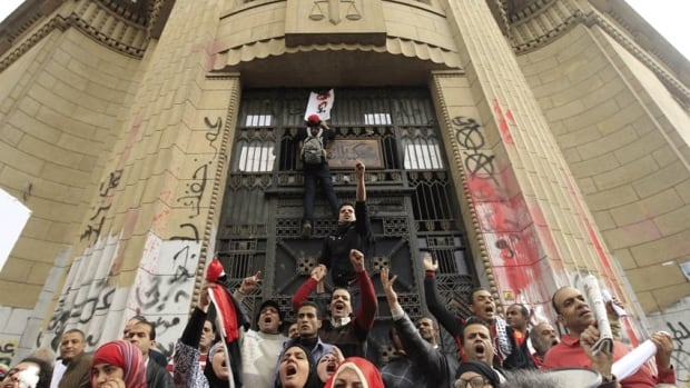 Protesters demonstrate against Egyptian President Mohamed Morsi in front of the courthouse and Office of the Attorney General, which has been graffitied with anti-government slogans.