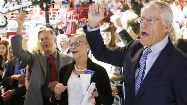 Members of the Walton family, founders of the retail giant Wal-Mart, recite the Wal-Mart cheer at the company's annual shareholders meeting in Fayetteville, Ark., where they faced scrutiny over the company's labour practices overseas. From left to right, Jim Walton, Alice Walton and Rob Walton, chairman of the board of directors.