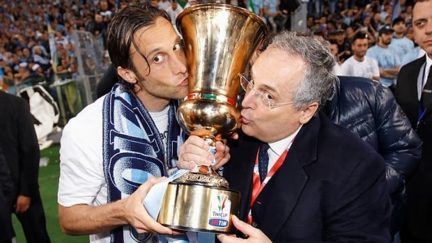 S.S. Lazio's Stefano Mauri, left, and team president Claudio Lotito kiss the Italian Cup trophy as they celebrate winning the Italian Cup final soccer match on May 26, 2013. Just over one month later, Lazio and their captain Mauri are facing charges in a match-fixing scandal.