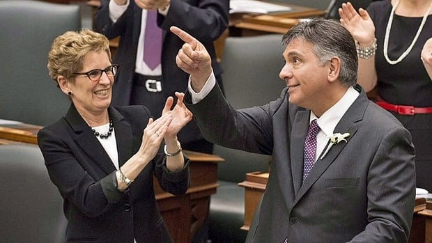 Ontario Premier Kathleen Wynne applauds Finance Minister Charles Sousa as he delivers the new provincial budget at Queen's Park in Toronto on Thursday.