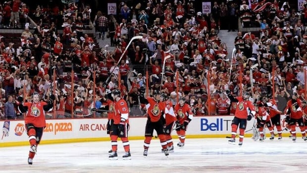 Ottawa Senators' Daniel Alfredsson, left, celebrates a win with teammates as fans cheer their win over the Montreal Canadiens after overtime in Game 4.