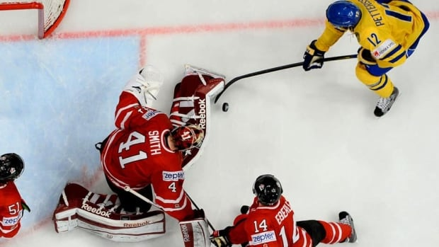 Canada goalie Mike Smith stops a shot by Sweden's Fredrik Pettersson, top right, during Thursday's game.