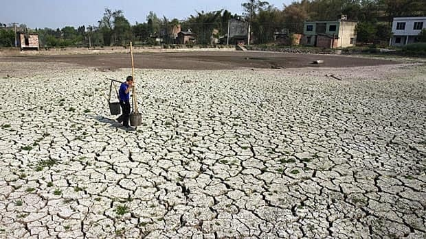 A farmer carries buckets past a partially dried-up pond in China's Sichuan province last month. A drought, now in its fourth year, has affected about 23.7 million people in Yunnan, Gansu and Sichuan provinces.
