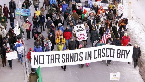Protesters march onto the Maine State Pier in Portland on Saturday, Jan. 26, 2013 to attend a rally against the possibility of tar sands oil being piped from Canada across northern New England to Portland, Maine.