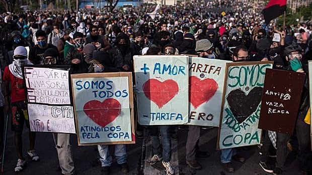 "People use protest signs as shields as they demonstrate outside Minerao stadium in Belo Horizonte on June 22. The sign reads ""More love, less fare,"" referring to the fares for public transportation."